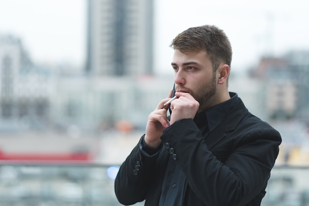Een zakenman rookt een sigaret en spreekt telefonisch over een stadslandschap.