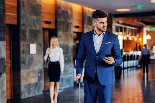 Een zakenman van middelbare leeftijd gekleed in formele kleding loopt in de lobby van een chique hotel. hij houdt een slimme telefoon vast en trekt een koffer.