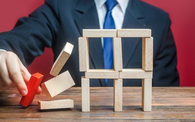 Een zakenman verwijdert een belangrijk onderdeel dat instorting van het hele complexe systeem veroorzaakt