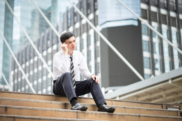 Een zakenman zit aan de trap en denkt aan iets.