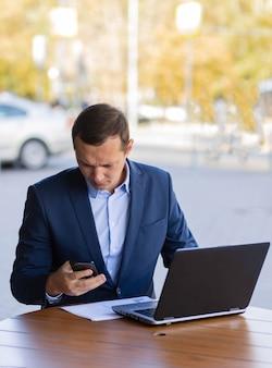 Een zakenman zit aan een tafel in een café op straat en praat tijdens een pauze van het werk tijdens een videogesprek op zijn mobiele telefoon