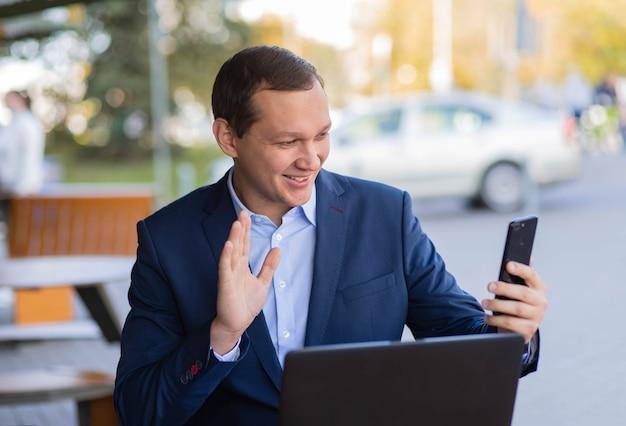 Een zakenman zit aan een tafel in een café op straat en zwaait met zijn hand tijdens een videogesprek naar zijn mobiele telefoon tijdens een pauze van zijn werk