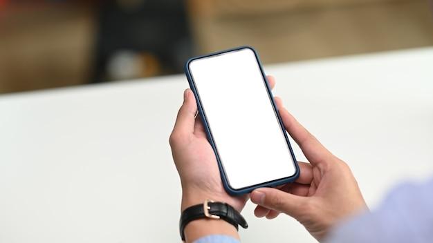 Een zakenmanhand die mobiele telefoon met wit scherm houdt.