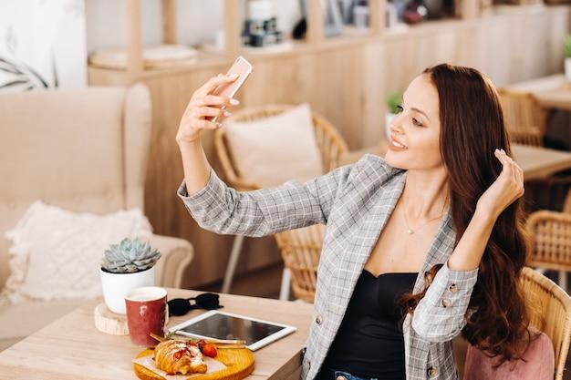 Een zakenmeisje zit in een café en neemt een selfie