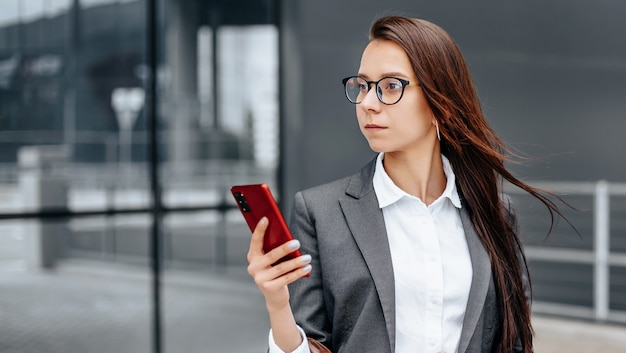 Een zakenvrouw controleert de tijd in de stad tijdens een werkdag in afwachting van een vergadering