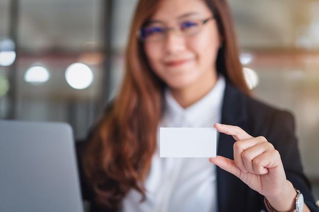Een zakenvrouw die een blanco visitekaartje vasthoudt en laat zien tijdens het gebruik van een laptopcomputer op kantoor