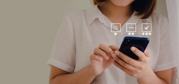 Een zakenvrouw die telefonisch een beoordeling maakt van de klantenservice in een bedrijfsidee met een pictogram op het scherm wachtend om te laden correct antwoord