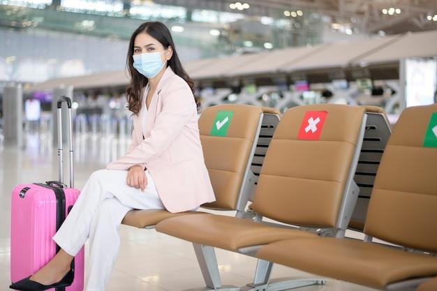 Een zakenvrouw draagt een beschermend masker op de internationale luchthaven, reist onder covid-19 pandemie, veiligheidsreizen, sociaal afstandsprotocol, nieuw normaal reisconcept