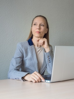 Een zakenvrouw droomt zittend op haar laptop