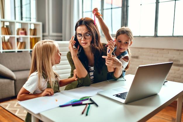 Een zakenvrouw en een moeder proberen op een laptop te werken terwijl haar kleine dochters spelen, voor de gek houden en zich met haar bemoeien. freelance, thuiswerken.