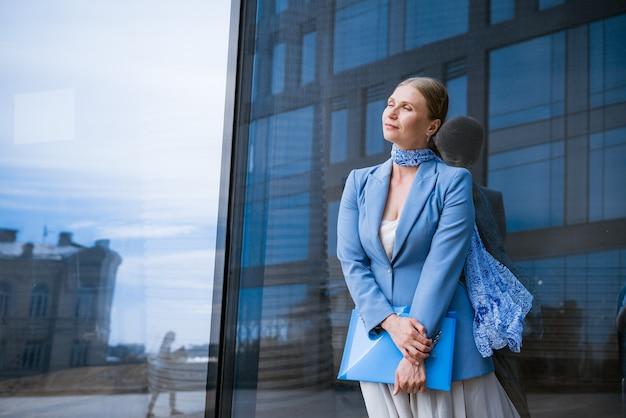 Een zakenvrouw in een blauw jasje houdt een map met papieren in haar hand voor een glazen kantoorgebouw