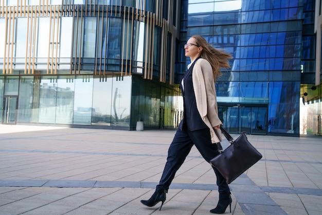 Een zakenvrouw in een jas en pak, met een tas in haar hand, loopt overdag in de buurt van het zakencentrum.