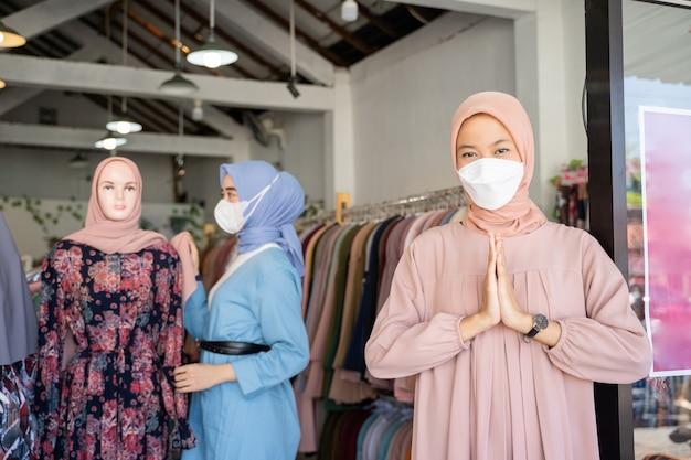 Een zakenvrouw in een sluier met een welkom gebaar terwijl ze staat
