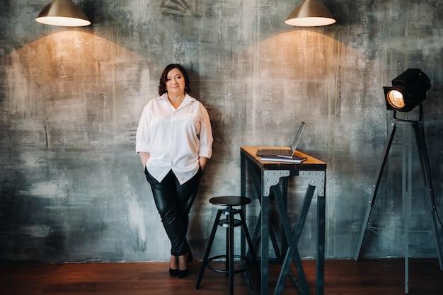 Een zakenvrouw in een wit overhemd en broek staat in haar kantoor.