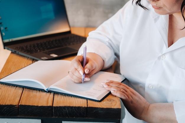 Een zakenvrouw in een wit overhemd zit aan een bureau en schrijft iets in een notitieblok op kantoor.