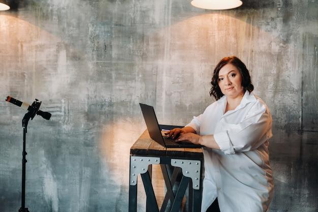 Een zakenvrouw in een wit overhemd zit aan een bureau en werkt op een laptop in het interieur.