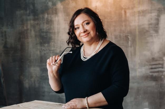 Een zakenvrouw in een zwarte jurk met kralen staat aan een bureau in haar kantoor.