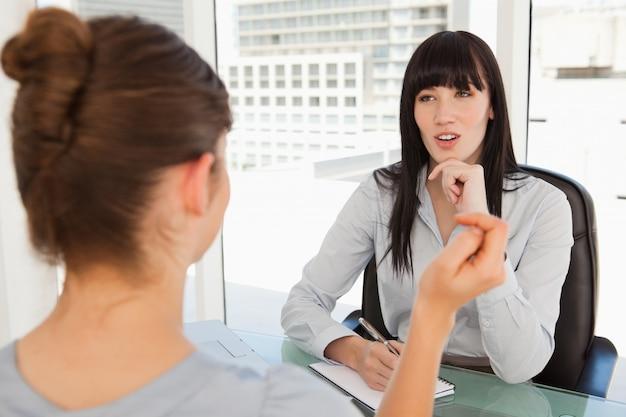 Een zakenvrouw luistert naar de andere vrouw in haar kantoor