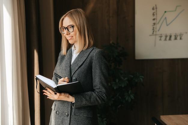 Een zakenvrouw met een notitieblok in haar handen staat glimlachend op kantoor, maakt aantekeningen en ontwerpt een nieuw businessplan voor het bedrijf dat door het panoramische raam kijkt.