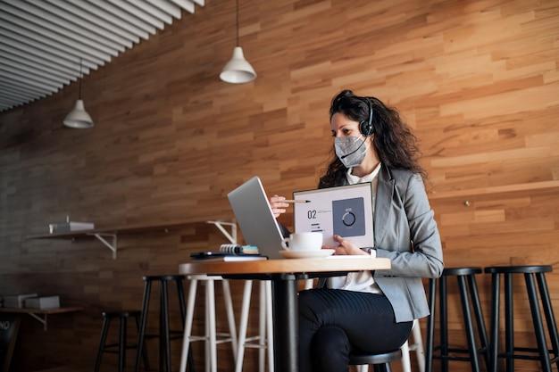 Een zakenvrouw met laptop die werkt in café, freelance werk en videogesprekconcept