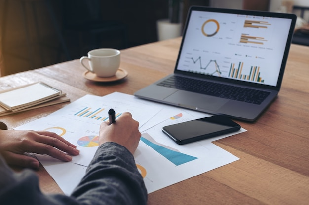 Een zakenvrouw schrijven en werken aan bedrijfsgegevens en documenten met laptop op de tafel in kantoor