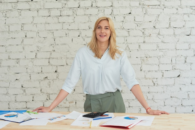 Een zakenvrouw staat aan een tafel met zakelijke rapporten en kijkt in de camera. ruimte kopiëren.