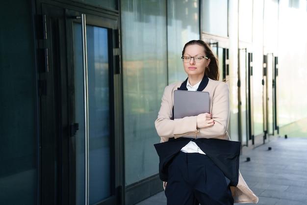 Een zakenvrouw staat overdag met een laptop in een pak en een bril buiten een kantoorgebouw.