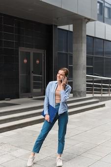 Een zakenvrouw staat tegen de achtergrond van het kantoorcentrum, glimlacht en spreekt aan de telefoon. communicatie met zakenpartners op afstand. jonge vrouwelijke zakelijke stijl