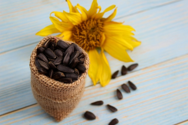 Een zakje staat met zonnebloempitten binnen op een houten tafel