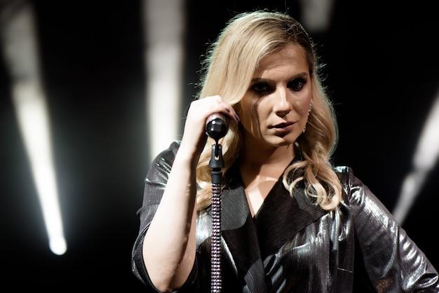 Een zangeres met lang haar houdt een microfoon met standaard en zingt.