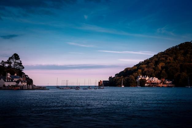 Een zee met schepen en gebouwen aan de kust, omgeven door hoge groene bergen in dartmouth, uk