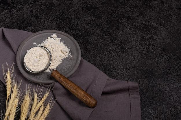 Een zeef met een houten handvat met bloem in een betonnen plaat op een zwarte achtergrond. oren van tarwe en een linnen servet. bakvoorbereiding