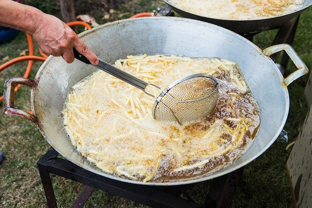 Een zeef vol frietjes laat men in de kokende olie zakken.