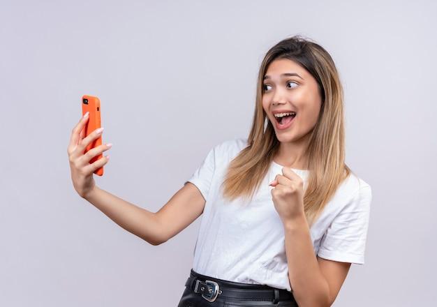 Een zeer gelukkige mooie jonge vrouw die in wit t-shirt mobiele telefoon bekijkt terwijl gebalde vuist wordt opgeheven