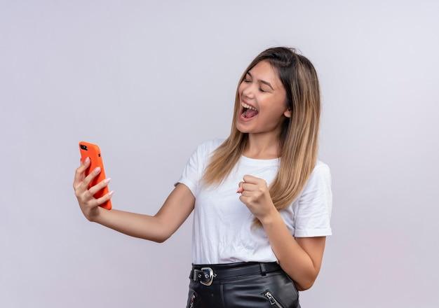 Een zeer gelukkige mooie jonge vrouw die in wit t-shirt mobiele telefoon houdt terwijl gebalde vuist opheft