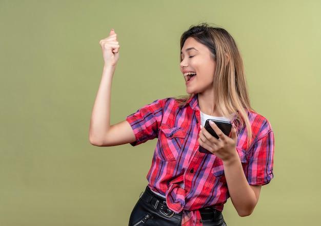 Een zeer gelukkige mooie jonge vrouw in een geruit overhemd die mobiele telefoon houdt terwijl gebalde vuist opheft