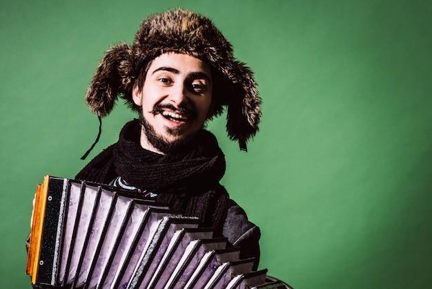 Een zeer positieve man met een accordeon poseren