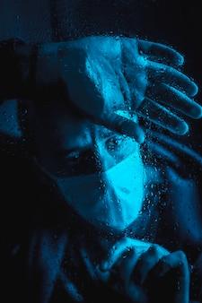 Een zeer trieste jongeman in de quarantaine van de covid 19 op een regenachtige nacht met een masker dat uit het raam kijkt, met blauw omgevingslicht