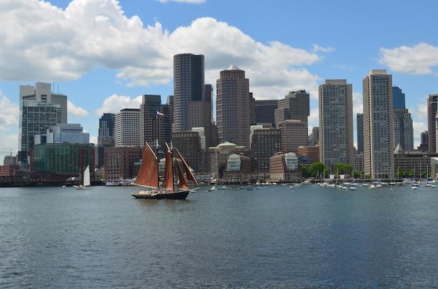 Een zeilboot die op een perfecte zomerdag in de haven van boston vaart.