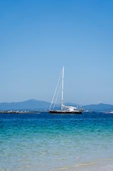 Een zeilboot in de buurt van een strand