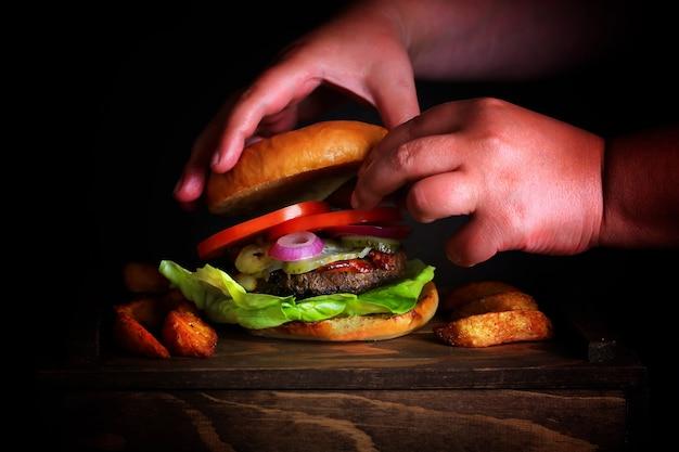 Een zelfgemaakte burger koken met zijn handen op de foto. donkere achtergrondfoto.