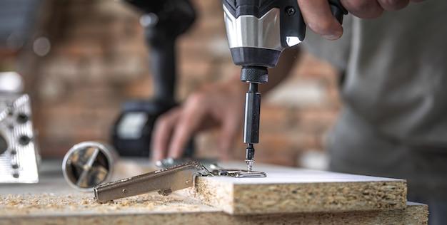 Een zelftappende schroef in een metalen bevestigingsgat op een houten strip schroeven met een schroevendraaier, het werk van een timmerman.