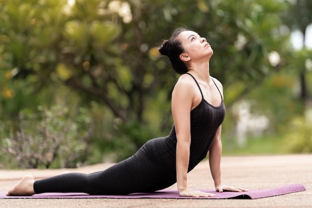 Een zelfverzekerde aziatische vrouw van middelbare leeftijd in een sportoutfit die yogaoefeningen doet op de yogamat buiten