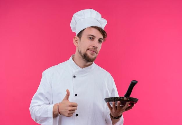 Een zelfverzekerde jonge bebaarde chef-kok in wit uniform duimen opdagen met een koekenpan in de andere hand terwijl hij op een roze muur kijkt