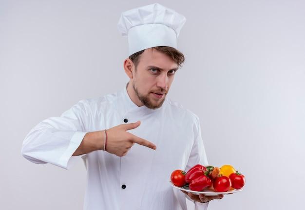 Een zelfverzekerde jonge bebaarde chef-kok man met een wit fornuis uniform en hoed wijzend op een witte plaat met verse groenten op een witte muur
