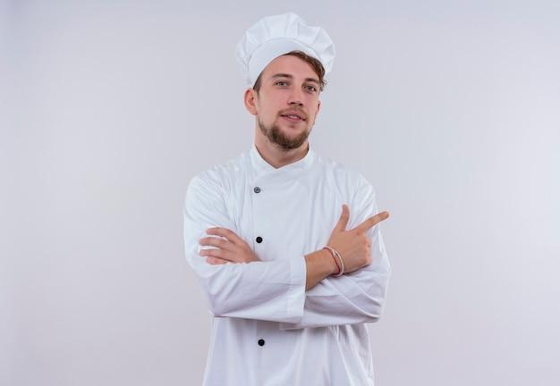 Een zelfverzekerde jonge bebaarde chef-kok man met wit fornuis uniform en hoed wijzend met wijsvinger en hand in hand terwijl hij op een witte muur kijkt