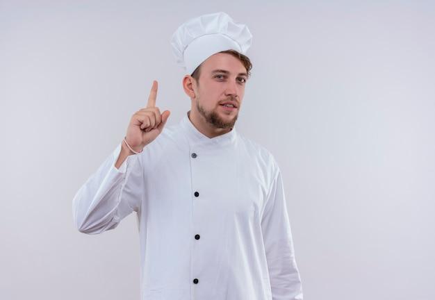 Een zelfverzekerde jonge, bebaarde chef-kokmens die een wit fornuisuniform draagt en een hoed die met wijsvinger omhoog wijst terwijl hij op een witte muur kijkt