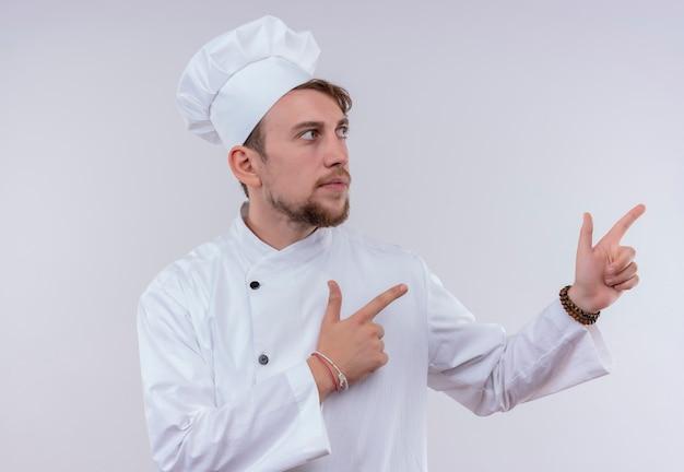 Een zelfverzekerde jonge, bebaarde chef-kokmens die een wit fornuisuniform draagt en een hoed die met wijsvingers omhoog wijst terwijl hij kant op een witte muur kijkt