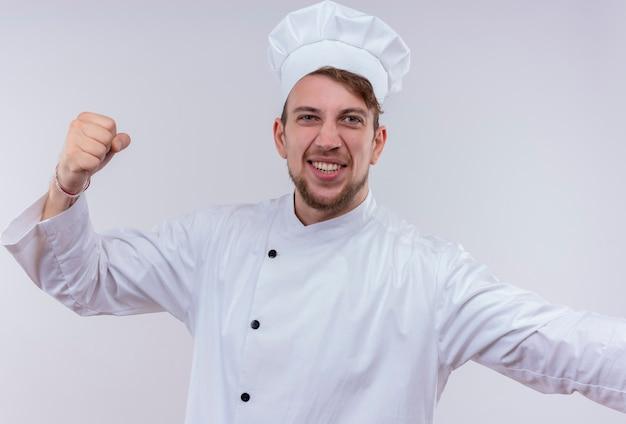 Een zelfverzekerde jonge, bebaarde chef-kokmens met een wit fornuisuniform en een hoed die gebalde vuist opheft terwijl hij op een witte muur kijkt
