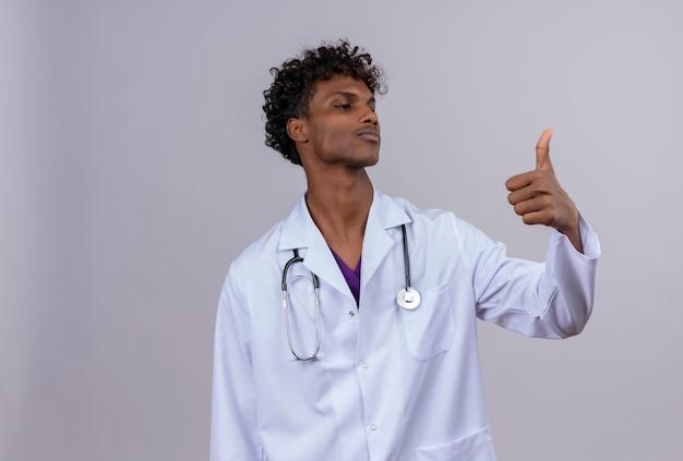 Een zelfverzekerde jonge knappe donkere arts met krullend haar, gekleed in een witte jas met een stethoscoop die duimen opdagen